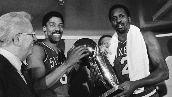 In this 1983 file photo, the Philadelphia 76ers' Julius Erving, left, and Moses Malone, right, hold the NBA championship trophy after defeating the Los Angeles Lakers.