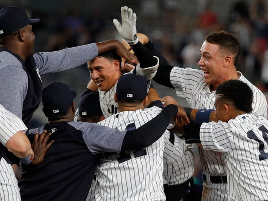 New York Yankees' Ronald Torreyes, center, celebrates with teammates after driving in Gary Sanchez with the winning run against the Texas Rangers during the 10th inning of a baseball game, Friday, June 23, 2017, in New York. The Yankees won 2-1. (AP Photo/Julie Jacobson)