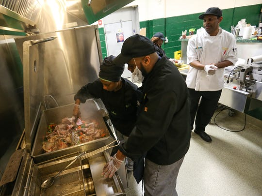 Gennie Tolliver, left, and Michael Risbrook prepare veal stock as chef Donnie Stephens watches during class at the Delaware Food Bank culinary school Thursday in Newark. The program provides job skills. Lawmakers are addressing poverty issues this year in the Statehouse.