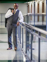 St. Georges principal Shanta Reynolds wears a gray three-piece wool suit with gold pinstripes from Macy's; white Charles Tyrwhitt shirt with French cuffs; Charles Tyrwhitt gold and blue paisley tie; Magnanni shoes from Nordstrom;