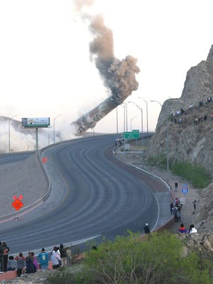 The huge Asarco smokestack falls during the 2013 demolition as spectators watch from the mountain next to the University of Texas at El Paso campus.