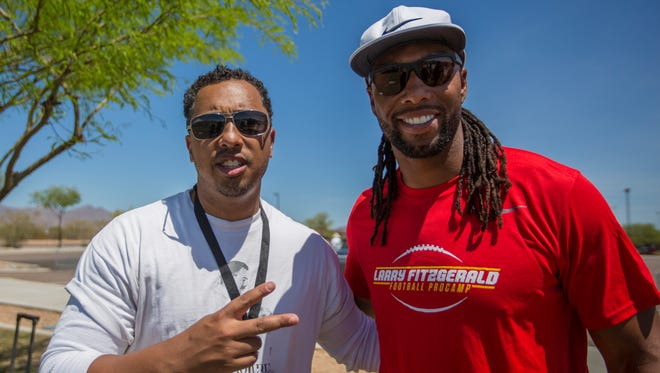 Arizona Republic sports columnist Greg Moore poses for a photos with Cardinals wide receiver Larry Fitzgerald after their challenge during the closing ceremony of the youth football camp in Fitzgerald's name, at Salt River Fields on Saturday, April 21, 2018.