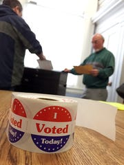Voters cast their ballots at the Town Meeting House in Colchester Village on Tuesday afternoon.