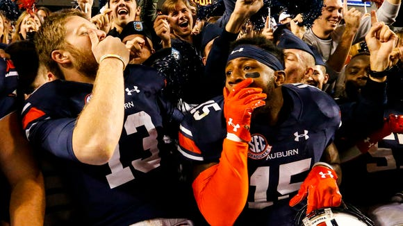 Auburn quarterback Sean White (13) and defensive back Joshua Holsey (15) celebrate after they defeated Arkansas 56-3 in an NCAA college football game, Saturday, Oct. 22, 2016, in Auburn, Ala. (AP Photo/Butch Dill)