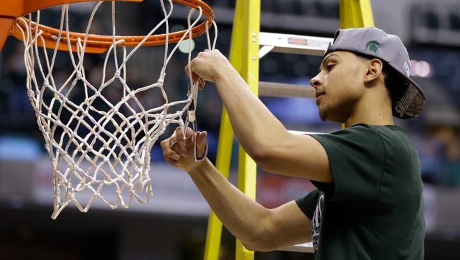 Bryn Forbes helps cut down the net after Michigan State defeated Purdue in the Big Ten championship game.