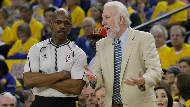 San Antonio Spurs head coach Gregg Popovich, right, talks with referee Tom Washington during the first half of Game 1 of the NBA basketball Western Conference finals between the Golden State Warriors and the San Antonio Spurs in Oakland, Calif., Sunday, May 14, 2017.