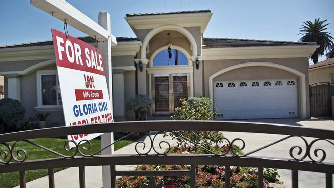 """A """"For Sale"""" sign is posted on a home in Monterey Park, Calif., in September 2014."""