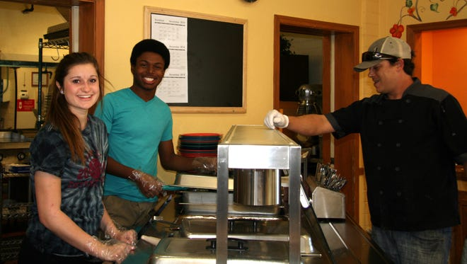 Zachary Edwards and Camy Cohn, members of the Desert Ridge Cares for Kids club, serve food at Sunshine Acres in Mesa.