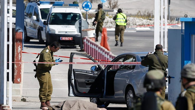 Israeli security forces inspect the body of a Palestinian identified as Amjad Sukkari, inside a car, at the checkpoint between the city of Ramallah and Jewish settlement of Beit El in the West Bank on Sunday.