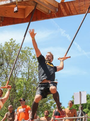 Jason Haddox of Pensacola reaches out to try and ring the bell at the King of the Swingers obstacle Saturday during the 2016 Tough Mudder event in Milton.