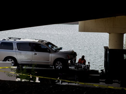 A worker prepares to tow a vehicle after it crashed