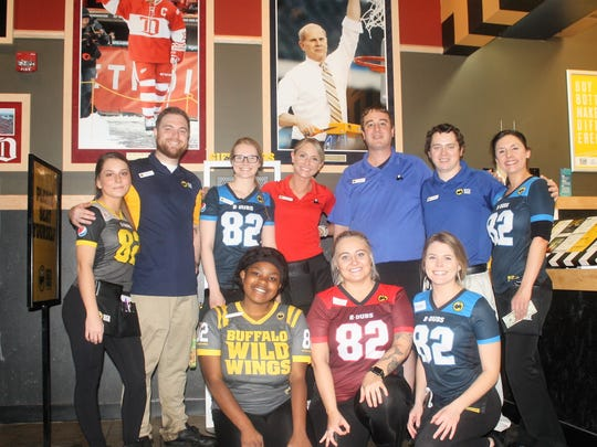 "The staff of the Canton-based Buffalo Wild Wings restaurant pose for a quick ""team"" photo during a quick break in their hectic Thursday afternoon shift."