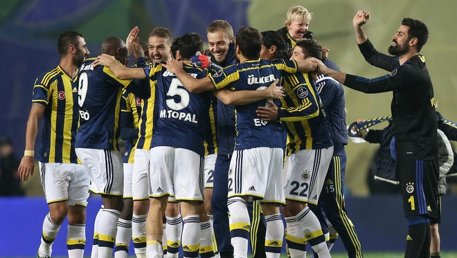 Fenerbahce's Dirk Kuyt holds up on his shoulder one of his three children as he celebrates with team mates after their Turkish League soccer derby match with Galatasaray at the Sukru Saracoglu Stadium in Istanbul, Turkey, Sunday, March 8, 2015