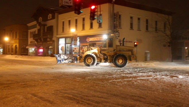 Snow removal equipment drives through a nearly deserted intersection on Main Street in Webster.