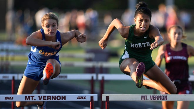 Castle's Addy Hawkes (left) and Ariah Leary clear the last hurdle in the 100 meter hurdles at the girls track sectional held at Mount Vernon High School Tuesday, May 16, 2017.