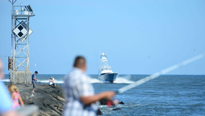 An angler tries his luck from land as deep sea fishing boats arrive from the Atlantic into the Ocean City Inlet.