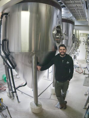 Grant Pauly, founder and brewmaster of 3 Sheeps Brewing Company, stands by one of his brewing kettles.