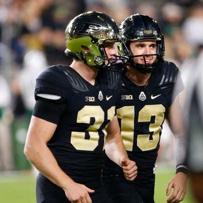 Purdue kicker Spencer Evans, right, celebrates with