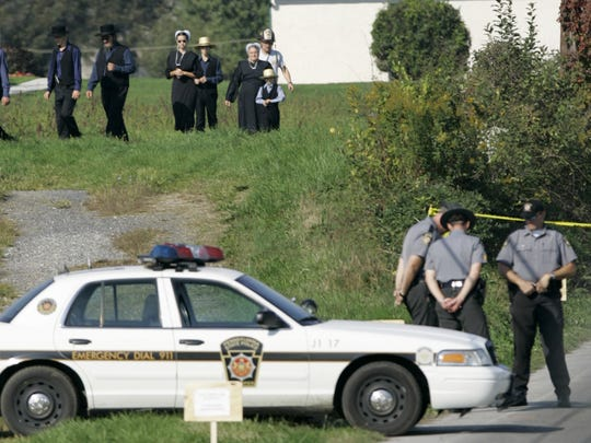 People are seen walking near the schoolhouse in Nickel Mines, Pa., Wednesday Oct. 4, 2006, where a gunman killed several people on Oct. 2. Charles Carl Roberts IV, a milk truck driver carrying three guns stormed the one-room Amish schoolhouse on Monday, sent the boys and adults outside, barricaded the doors with two-by-fours, and then opened fire on several girls before committing suicide. Another child died Tuesday morning of wounds from the shootings, raising the death toll to five girls plus the gunman who apparently was spurred by a two-decades-old grudge.