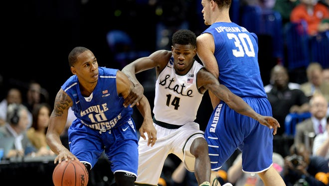 Michigan State junior guard Eron Harris (14) fights through a screen by Middle Tennessee junior forward Reggie Upshaw Jr. (30) as he defends Middle Tennessee senior guard Jaqawn Raymond (10) during a first round NCAA Tournament game between second-seeded Michigan State and 15-seeded Middle Tennessee Friday, March 18, 2016 at the Scottrade Center in St. Louis.