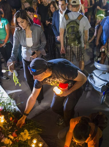 Mourners lay flowers and candles for victims of the Texas school shooting at a makeshift memorial during a vigil at the Arizona State Capitol May 21, 2018. Ten people were killed when a student opened fire inside Santa Fe High School May 18.