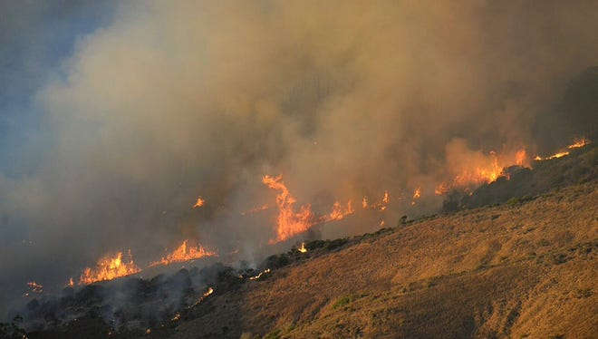 Flames from the canyon fire advance Sunday evening on Vandenberg Air Force Base's south base. Over 2200 acres have burned.