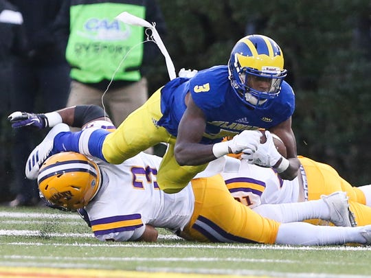 Delaware's Joe Walker is tripped up after a gain by Albany's Justin Walker in the second quarter at Delaware Stadium Saturday.