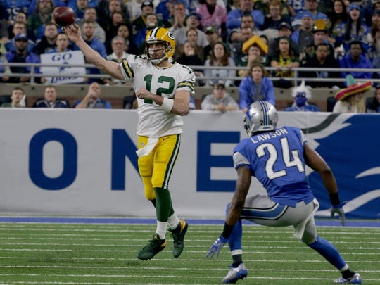 Packers quarterback Aaron Rodgers throws downfield as Lions cornerback Nevin Lawson looks on during the first half Sunday at Ford Field.