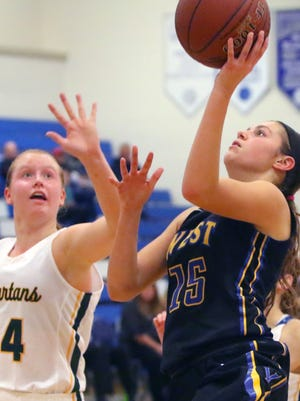 New Berlin West's Alyssa Nelson lays up two points past Martin Luther's Bonnie Jensen at the Brookfield Central Thanksigving Shootout on Nov. 25. West hosts Greendale on Friday, and Martin Luther hosts Racine Prairie on Saturday.