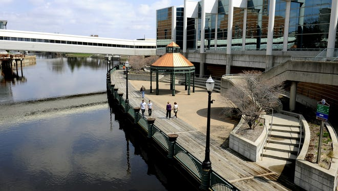 People enjoy the River Trail along the Grand River in downtown Lansing.