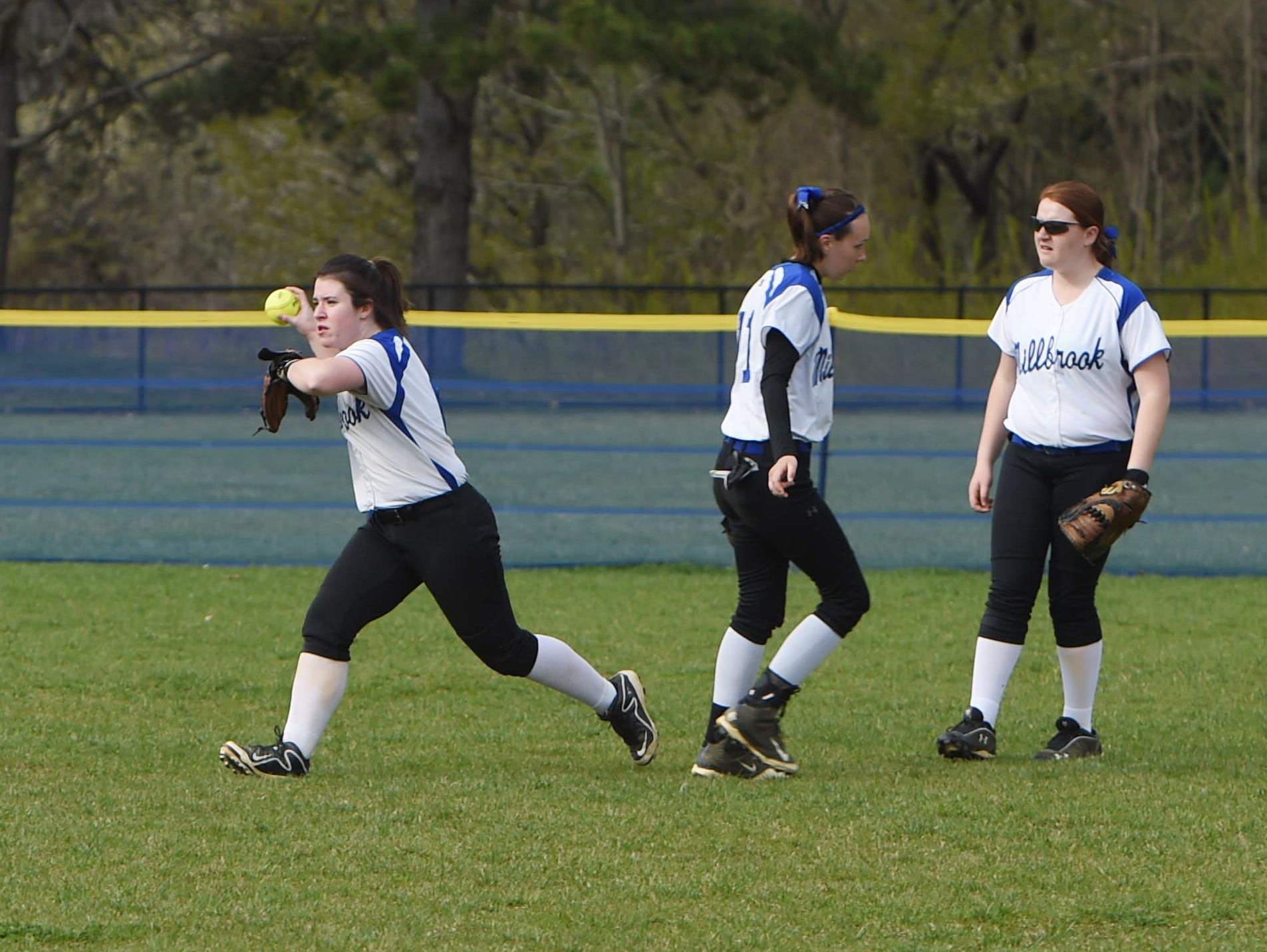 Millbrook's Abby Hackbarth, left, goes to throw the ball to the infield while teammates Ciera Lamont, center, and Tiffany Race, right, get back into position during Monday's game against Pine Plains.