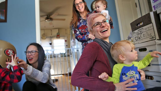 Christie Koester, right, holding her son Max, talks about some of the donations, right, given to Do Good Indy, during the group's play date, Wednesday, February 16, 2017.  The group gathers donations, does supply drives and volunteer opportunities as a way to give back to the community.  The founders of the Do Good Indy group are all mothers with young children.