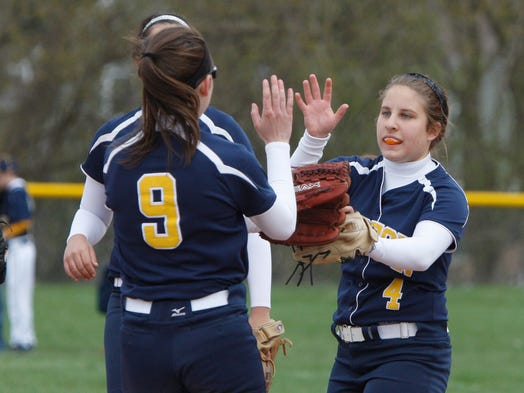 Victor starting pitcher Nicolette Kulakowski, right, gets a high-five from teammate Victoria Allocco, left, after striking out Fairport's Sarah Simmons during the second inning.
