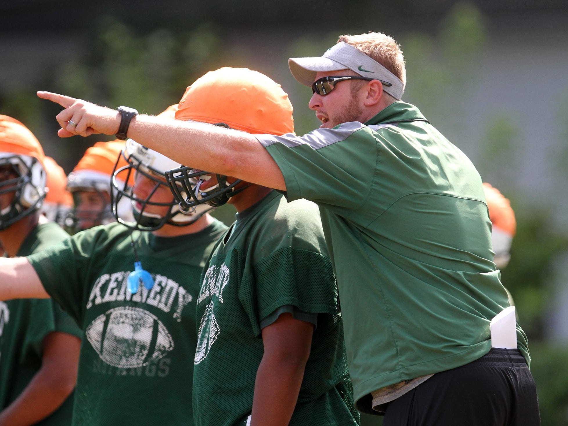 J.F. Kennedy head coach Andrew Maurizio works with his team during preseason football practice, Monday, August 25, 2014, in Woodbridge, NJ. Photo by Jason Towlen