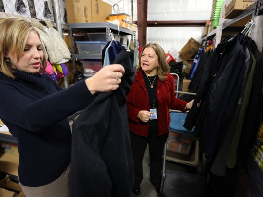 Eileen Woodside, a social worker with Rutherford County Schools, left, picks up a winter coat in 2014 for a student from Kim Snell, coordinator of the county school system's ATLAS program, which works to assist homeless students.