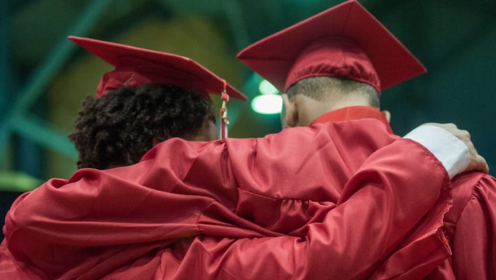 Two Everett graduates wrap arms after receiving their