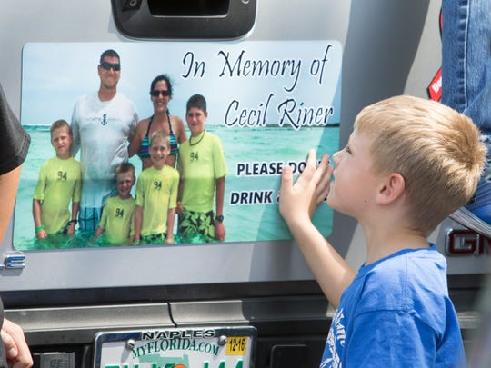 Braden Riner, 5, looks at a magnet with his family's portrait on the back of a vehicle prior to the charity ride to raise money for the Riner family in Naples on Saturday, March 26, 2016.  Cecil Riner who was killed in a December car crashed caused by an alleged drunk driver leaves behind his wife Jessica and four sons Landon, 11, Garret, 9, Carsen, 7, and Braden, 5.