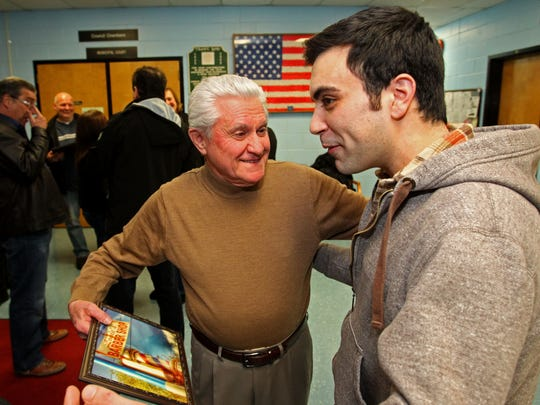 """(left to right) Luigi Guarnieri receives a photo from Mike Florio, a customer for twenty five years. Luigi """"Louie"""" Guarnieri was being honored by UB council for his nearly six decades of business in the borough. Lou's Barbershop was destroyed in the fire at Hydrair in June when firefighter Bob """"Hawk"""" Meyer suffered a fatal heart attack. Louie, 76, first worked at the barbershop in 1956 before buying it a few years later. Thursday, January 22, 2015. Union Beach,NJ Noah K. Murray-Special for the Asbury Park Press ASB 0120 union beach barber retires"""