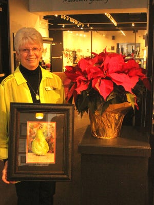 """Former """"Artist of the Month"""" at the Mesquite Fine Arts Gallery stands with her painting of a pear."""