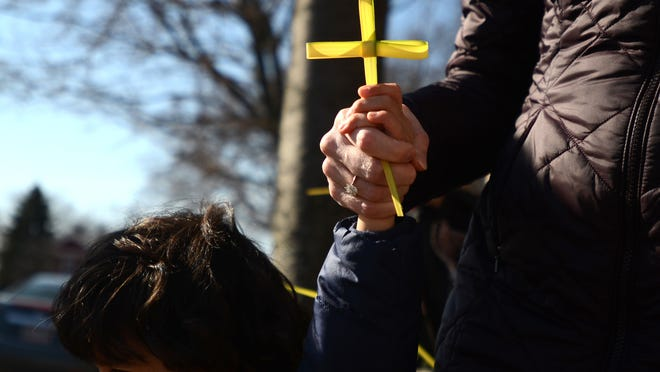 A women and child hold hands with a palm cross in-between their hands during Palm Sunday service at Grace Episcopal Church in Port Huron.