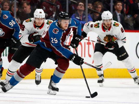 Colorado Avalanche center Nathan MacKinnon, front, picks up a loose puck as Chicago Blackhawks right wing Patrick Kane, back left, and center Nick Schmaltz pursue in the first period of an NHL hockey game Friday, March 30, 2018, in Denver. (AP Photo/David Zalubowski)