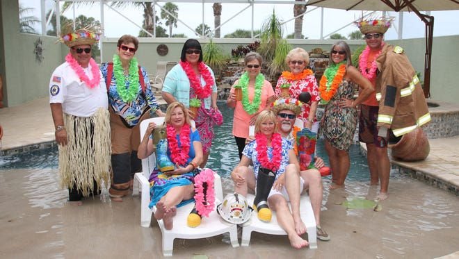 """Flip Flops and Leis"" planners and sponsors, from left, St. Lucie Fire Chief Nate Spera, Jane Rowley, Crystal Samuel, Deb LaBella, Pat Alley, Brenda Stokes, and Travis Leonard. Seated: Sue Dannahower, and Sandee and Art Allen."