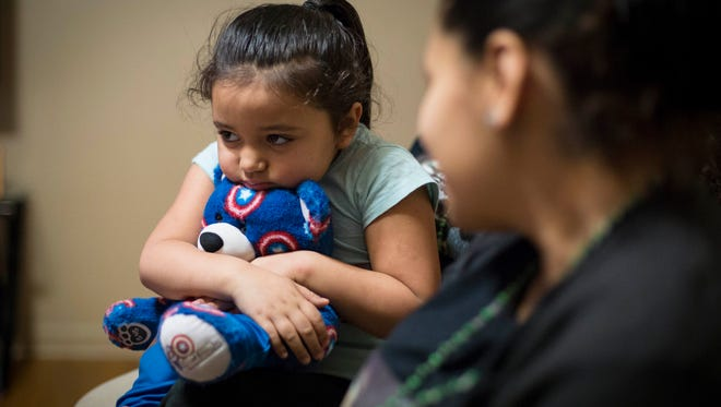 Edmanuel Perez's daughter Esette Perez, 4 years old, holds a Capt. America teddy bear Wed. Dec. 23, 2015, while family talks about how they have coped with his death since the Nov. 29 shooting in the Court Avenue entertainment district. Esette keeps her father's billfold inside the stuffed animal with a voice message to him.