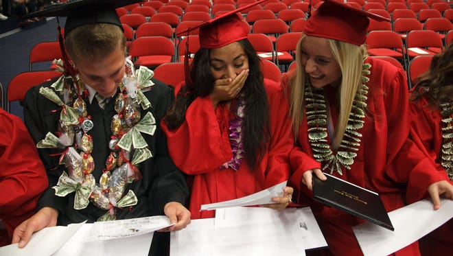 Hurricane High School senior Kimberly Hernandez reacts with joy at seeing her name on her high school diploma after walking across the stage during her school's commencement exercises Thursday, May 21, 2015 at Burns Arena on the campus of Dixie State University.