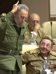 In this June 26, 2002, file photo, Cuba's leader Fidel Castro, left, votes in favor of the modification on the Cuban Constitution, as his brother, then-Defense Minister Raul Castro, looks on during a National Assembly session.