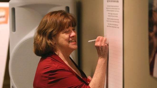 Jean Carroll, president and CEO of the YWCA of Rochester & Monroe County, signs a pledge against racism at the YWCA's annual Stand Against Racism event.