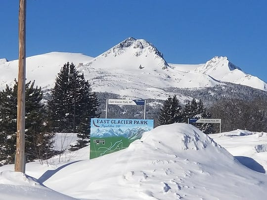 The sign welcoming motorists to East Glacier Park is nearly covered by a snow drift