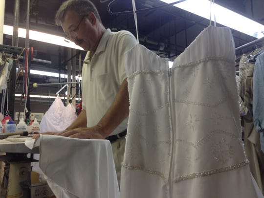 Tim Jolliffe, 57, operates the Thomas Street Classic Cleaners, and often works with his employees. On Friday, Aug. 22, he works to remove dance floor dirt stains from a wedding dress.