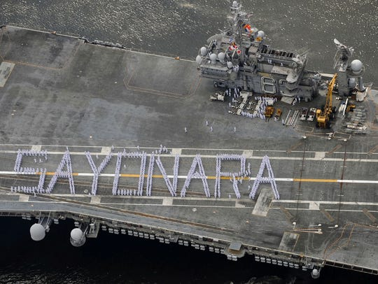 "Crew members aboard the USS Kitty Hawk formed the word ""sayonara,"" when the U.S. aircraft carrier departed a port near Tokyo for the final time in 2008."
