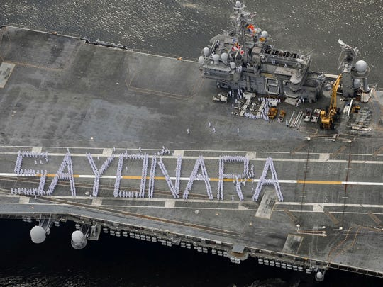 """May 30, 2008 FILECrew members aboard the USS Kitty Hawk form the word """"sayonara,"""" at top, as the U.S. aircraft carrier leaves a port near Tokyo on Wednesday. Above, sailors wave farewell Wednesday. The ship departed Japan to be decommissioned after nearly half a century of service."""